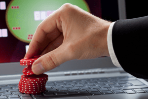 A hand raising a stack on a laptop keyboard