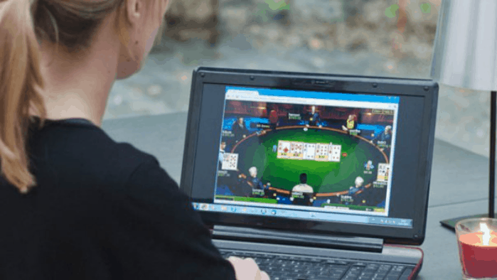 A young woman playing online poker on a laptop